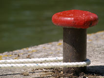 Canal-side mooring bollard. Old canal-side red mooring bollard with rope Stock Photography