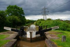 Canal Storm Brewing. Canal lock and pylon on a stormy day Royalty Free Stock Image