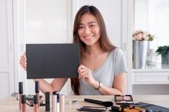 Canal suivant de jeune de blogger de don fan femelle asiatique de cadeau tout en enregistrant la vid?o de vlog avec du cosm?tique image libre de droits