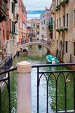Canal surrounded by old palaces in Venice. Bridges on a narrow canal surrounded by old decaying palaces in Venice Royalty Free Stock Photo