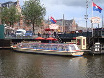 Canal tour boat on Amsterdam Canal. Tour boat docked on Amsterdam Canal near central railroad station awaits tourists royalty free stock image