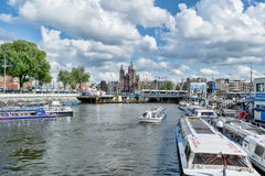 Canal and tour-boat in Amsterdam on sunny day Royalty Free Stock Images