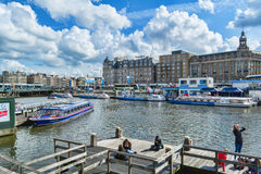 Canal and tour-boat in Amsterdam on sunny day Stock Photography