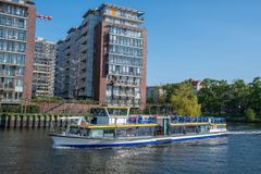 Canal tour boat sailing by residential buildings on river Spree. Berlin Germany - April 20. 2018: Canal tour boat sailing by residential buildings on river Spree stock photos