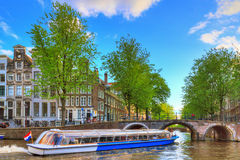Canal tour bridge. Canal cruise boat goes under the bridge over the Leidse canal at the Patricians' or Lords' canal (Herengracht) in Amsterdam in spring stock photos