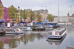 Canal Tours by Boat, Amsterdam. Boat cruise station downtown Amasterdam Royalty Free Stock Photo