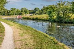 A canal with a tow path and a canal barge. royalty free stock images