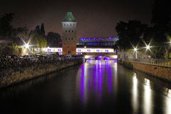 The Canal Tower. Night with a canal guard tower, in the historic district of Petite France in Strasbourg, with purple lights reflected in the water Royalty Free Stock Photography