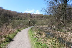 Canal towpath. A track alongside a disused canal full of overgrown vegetation Royalty Free Stock Photos