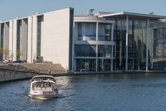 Canal trip boat sailing in front of of the Paul Lobe house. Berlin Germany - April 20. 2018: Canal trip boat sailing in front of of the Paul Lobe house stock photo