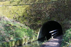 Canal Tunnel. A view of a canal towpath tunnel with moss and vegetation clinging to the surface of the tunnel structure Royalty Free Stock Images