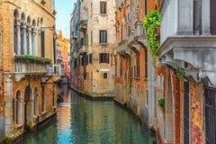 Canal veneciano con la góndola y las fachadas coloridas de casas medievales viejas en Venecia, Italia imágenes de archivo libres de regalías