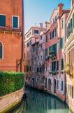 Canal veneciano estrecho con agua esmeralda A lo largo del canal son los edificios residenciales brillantes foto de archivo