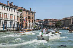 A canal in Venice/blue skies and waters and a boat. Royalty Free Stock Photo