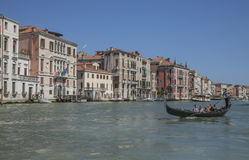 A canal in Venice/blue skies and waters and a gondola. Stock Photos