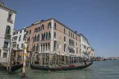 A canal in Venice/blue waters and skies, gondolas and historic buildings. Royalty Free Stock Images