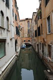 Canal in Venice with docked gondola and boats, Royalty Free Stock Images