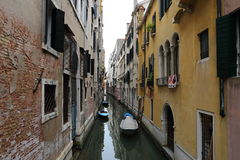 Canal in Venice with docked gondola and boats, Stock Photography