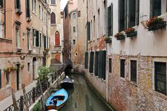 Canal in Venice with docked gondola and boats, Stock Photos