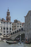 A canal in Venice/gondolas on the blue waters and the Rialto Bridge. Stock Photo