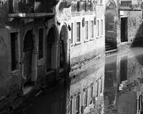 Canal in venice with reflections of buildings old walls doors an Stock Image