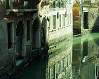 Canal in venice with reflections of buildings old walls doors an Stock Photography