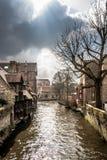 Canal vergonzoso que serpentea a través de Brujas medieval Fotografía de archivo