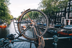 Canal view in Amsterdam, view through bicycle wheel parked on br Royalty Free Stock Images
