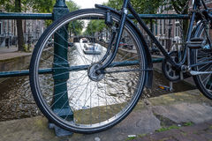 Canal view in Amsterdam, view through bicycle wheel parked on br Stock Photo