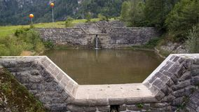 Canal of water barriers small pond on alps stock photos