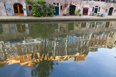Canal wharfs of Utrecht Netherlands. Canal and cellar wharfs in Utrecht, Netherlands. Vintage houses reflecting in water at sunset Stock Image