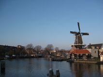 A canal and windmill view in Haarlem stock photography