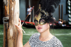 Canal and Woman wearing Venetian mask. Beautiful woman in front of canal wearing a Venetian mask Stock Images