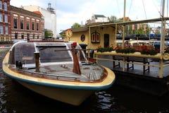 Canal y barco de Amsterdam para la ciudad que visita Imagenes de archivo
