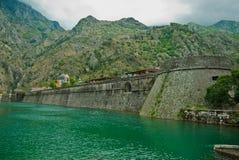 Canale della città del Montenegro Cattaro, parete dalle vecchie fortificazioni fotografie stock libere da diritti