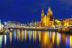 Canale di Amsterdam di notte e san Nichola della basilica immagine stock
