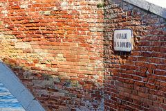 Canale di San Donato sign on brick wall, Murano, Italy. Canale di San Donato road name sign on red brick wall, Murano island, Venice, Italy stock image