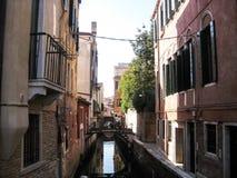 Canale stretto fra le case con mattoni a vista a Venezia fotografia stock