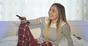 Canales cambiantes de la mujer alegre en la TV teledirigida almacen de metraje de vídeo