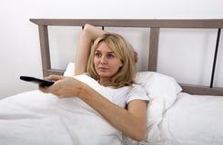 Canales cambiantes de la mujer joven con teledirigido en cama Imagenes de archivo