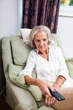 Canales cambiantes de la mujer mayor con teledirigido en la butaca en casa Imágenes de archivo libres de regalías