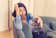 Canales de televisi?n cambiantes agujereados de la mujer con teledirigido imagen de archivo