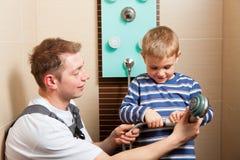 Canalizador que instala uma torneira de misturador em um banheiro foto de stock royalty free