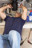 Canalizador que trabalha no dissipador fotografia de stock