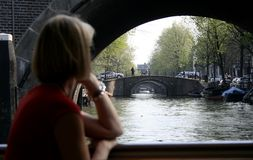 Canals of Amsterdam. Lady look at endless bridges across Amstel river Royalty Free Stock Images