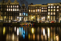 Canals in Amsterdam at Night and a Colorful Boat Royalty Free Stock Images