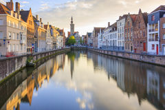Canals of Bruges, Belgium. Canals of Bruges in a sunny spring afternoon with the church of our lady in the background, Bruges, Belgium Stock Images