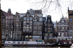 Canals houses at the river amstel and a house boat Royalty Free Stock Images