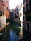 Canals of Venice. A canal in Venice, Italy, with an approaching Gondola Royalty Free Stock Image