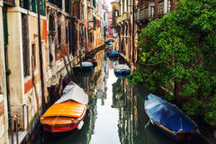 Canals in Venice, Italy. Boats moored in front of the houses Stock Photos